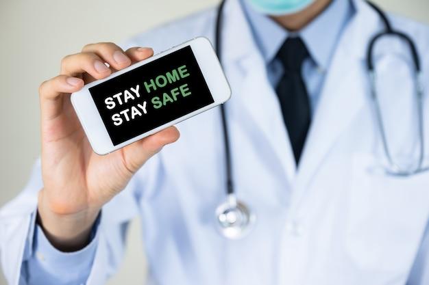 Médico mão segurando o telefone móvel com ficar em casa ficar mensagem segura