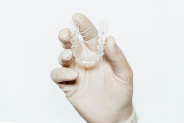 Médico mão segurando um alinhador dental claro