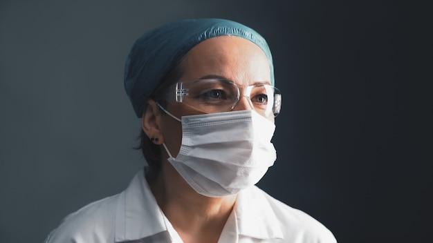 Médico mascarado em óculos de proteção, olhando de lado. meados envelhecida mulher caucasiana em jaleco branco sobre fundo cinzento escuro. feche o retrato. conceito de saúde. imagem enfraquecida.