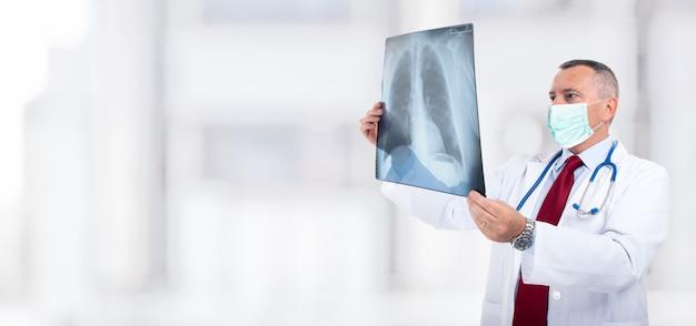 Médico mascarado segurando uma radiografia pulmonar, conceito de coronavírus e pneumonia