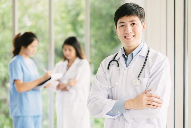 Médico masculino asiático na frente de equipes médicas