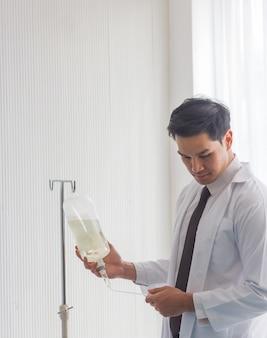 Médico masculino asiático, olhando para uma garrafa de solução salina para verificar a disponibilidade do dispositivo