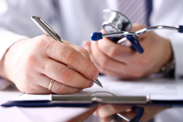 Médico masculino braço segurar caneta e bloco de prata
