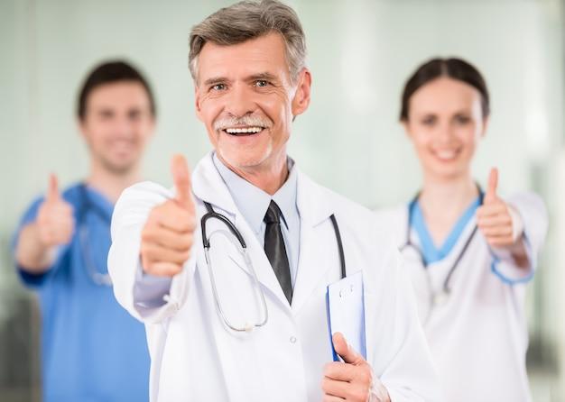 Médico masculino com colegas sorrindo.