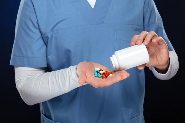 Médico masculino com comprimidos na mão