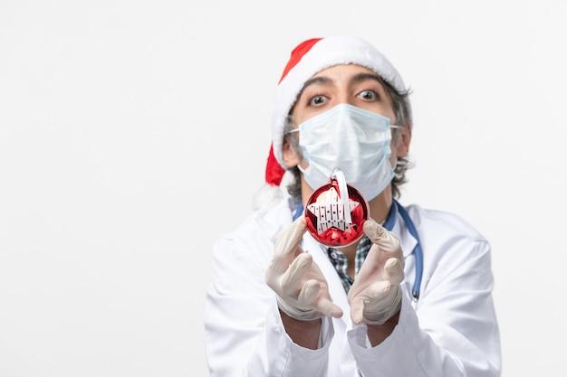 Médico masculino com máscara e brinquedo no chão branco saúde cobiça vírus de ano novo
