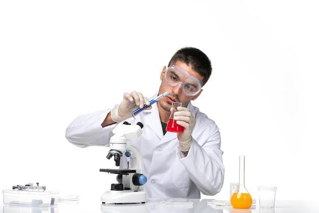 Médico masculino com terno branco trabalhando com soluções na mesa branca