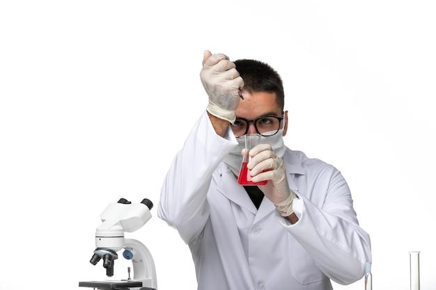 Médico masculino de vista frontal com terno branco e máscara devido a ambicioso trabalhar com soluções na mesa branca