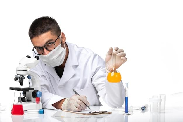 Médico masculino de vista frontal com terno branco e máscara trabalhando com soluções no espaço em branco