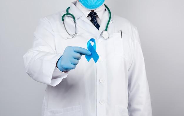Médico masculino em um casaco branco e gravata fica e detém uma fita de seda azul