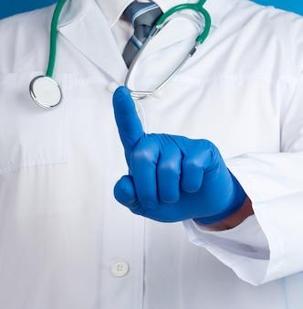Médico masculino em um jaleco branco e luvas azuis de látex fica em um fundo azul e com a mão direita estica o dedo indicador para a frente
