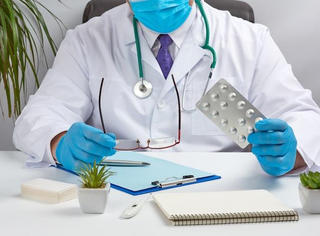 Médico masculino em um jaleco branco e luvas azuis de látex senta-se em uma mesa branca em seu escritório e mostra um pacote de comprimidos em uma bolha