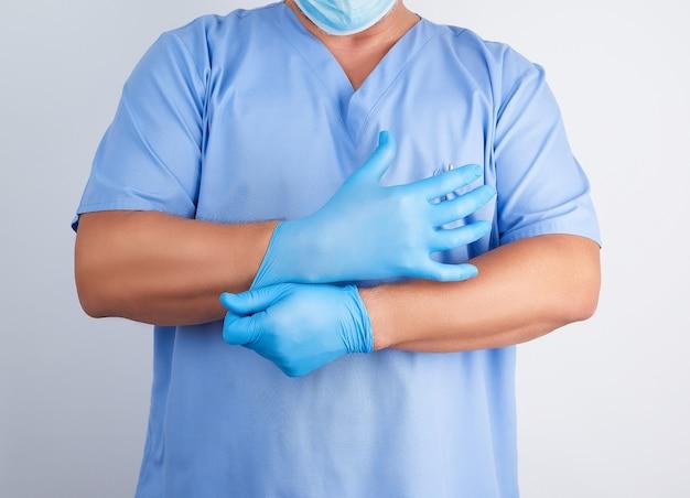 Médico masculino em uniforme azul coloca em suas mãos luvas de látex estéreis brancas antes da cirurgia