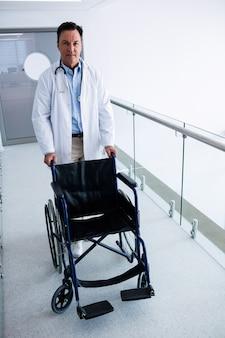 Médico masculino empurrando uma cadeira de rodas vazia na passagem