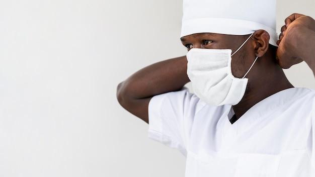 Médico masculino especialista, colocando o retrato da máscara