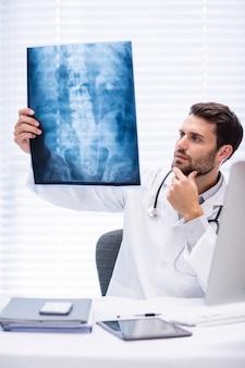 Médico masculino, examinando o raio-x