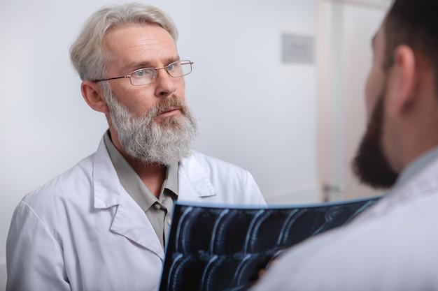 Médico masculino idoso discutindo ressonância magnética de um paciente com um colega de trabalho