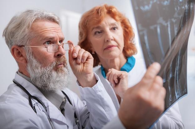 Médico masculino idoso e enfermeira feminina sênior examinando a ressonância magnética juntos