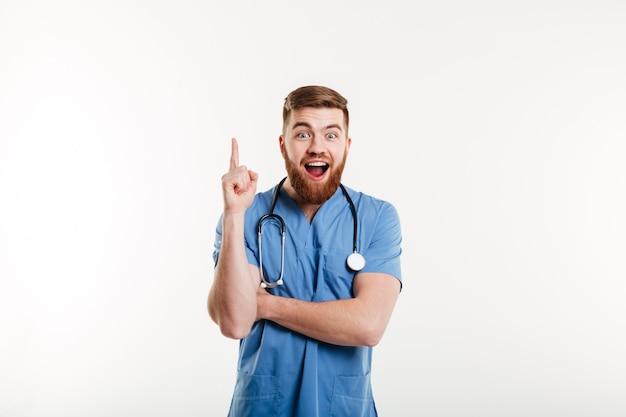 Médico masculino jovem animado apontando o dedo para cima na copyspace