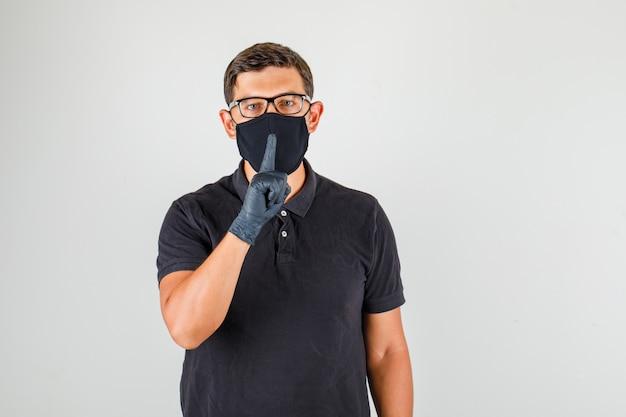Médico masculino mostrando o gesto de silêncio na camisa polo preta