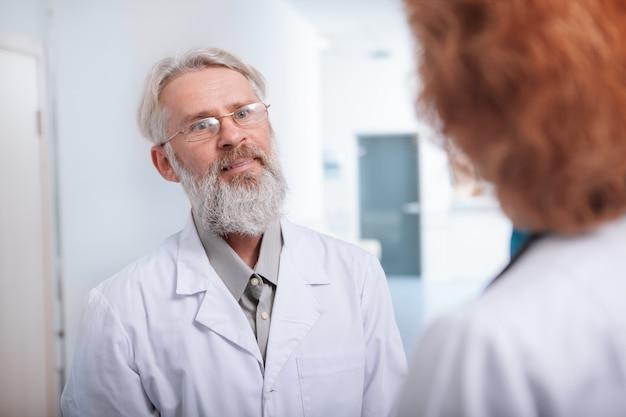 Médico masculino sênior feliz sorrindo, conversando com uma colega na sala da clínica
