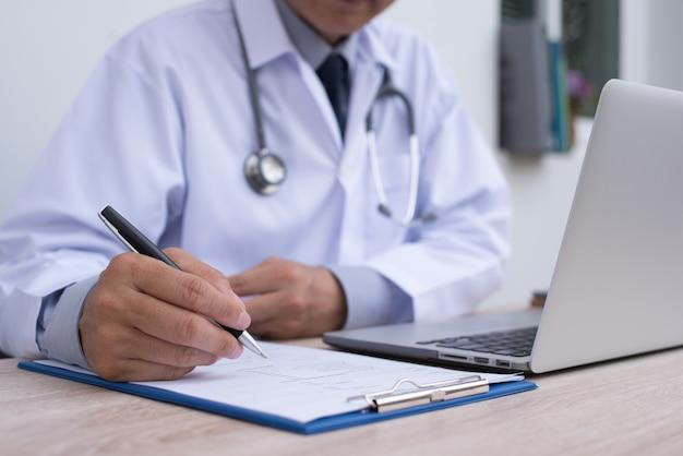 Médico masculino trabalhando no computador portátil e preenchendo documentos médicos