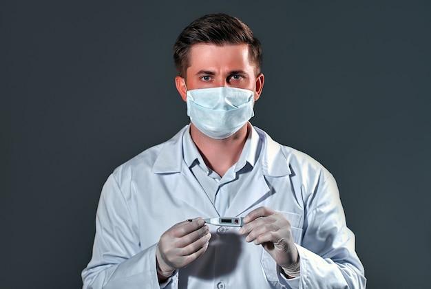 Médico masculino usando luvas e máscara mostrando termômetro.