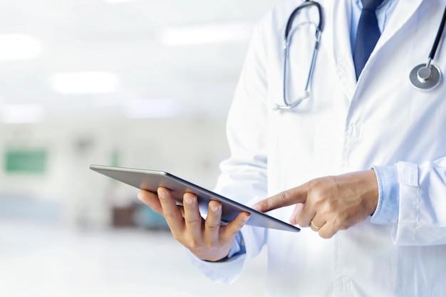 Médico masculino usando seu tablet digital na consulta. conceito de medicina e saúde