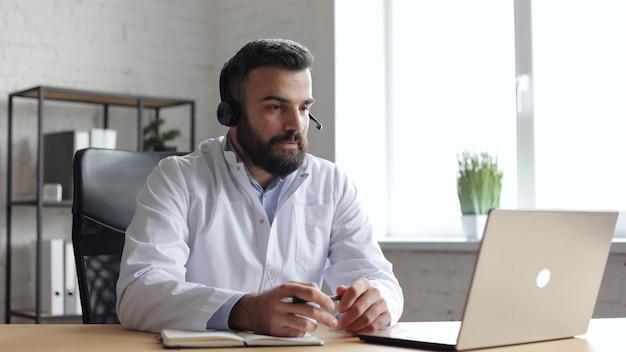 Médico masculino vestindo jaleco branco, consultando o paciente remotamente on-line usando fone de ouvido e câmera web no laptop.