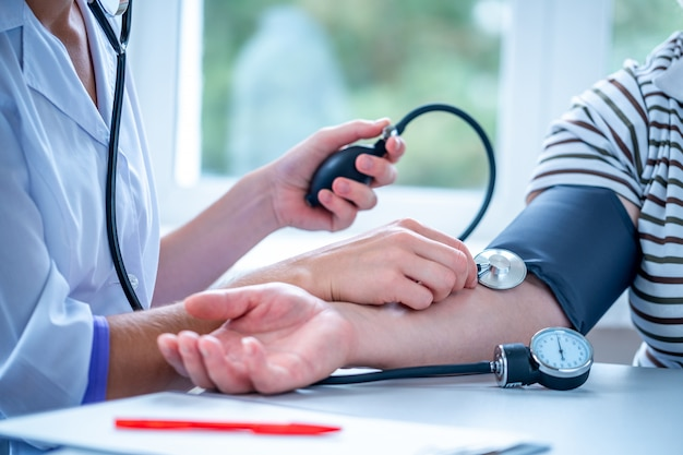Médico mede a pressão do paciente durante um exame médico e consulta no hospital.