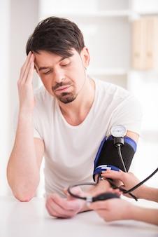 Médico mede a pressão para jovem com dor de cabeça.