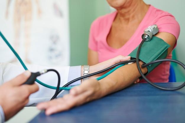 Médico mede pressão em paciente idoso