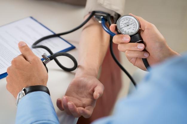 Médico mede pressão no paciente