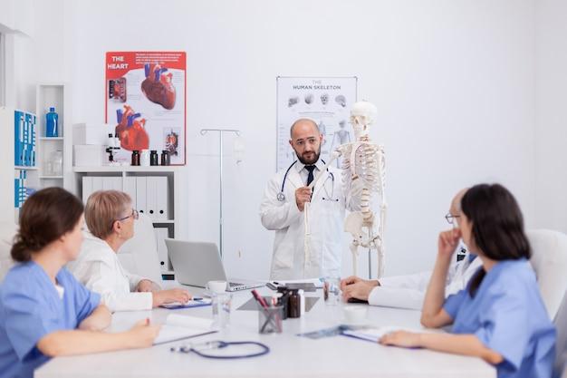 Médico médico com estetoscópio segurando o osso da mão, explicando o esqueleto humano do corpo, apresentando a estrutura da anatomia, discutindo a perícia médica. equipe do hospital trabalhando na sala de conferências