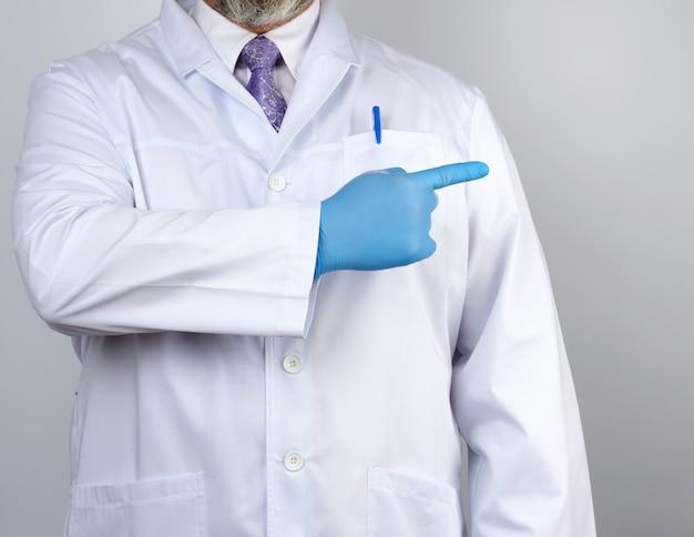 Médico médico de jaleco branco com botões, nas mãos usando luvas estéreis azuis, mostrando o gesto com a mão indicando o assunto
