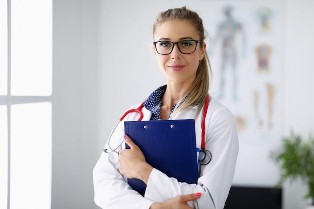 Médico médico sorri e mantém a área de transferência nas mãos.