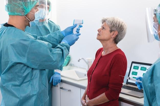 Médico medindo febre para uma mulher idosa antes da vacinação contra o coronavírus