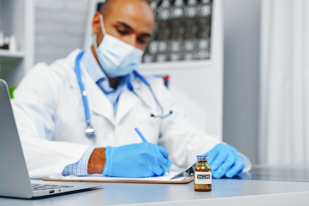 Médico mestiço sentado à mesa de trabalho no hospital