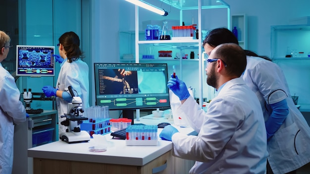 Médico microbiologista retirando um tubo de amostra de sangue da prateleira com máquinas de análise no fundo do laboratório