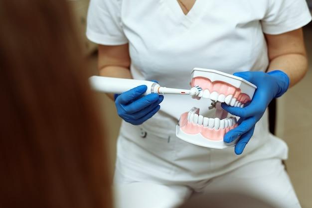 Médico mostra ao paciente como escovar corretamente os dentes com uma escova elétrica de forma clara