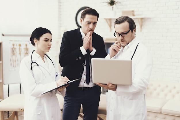 Médico mostra no laptop resultados de exame médico.