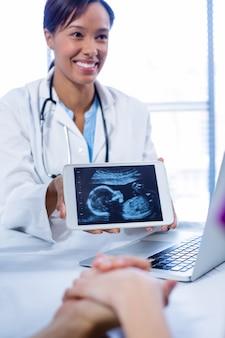 Médico mostrando bebês ultra-sonografia digital tablet