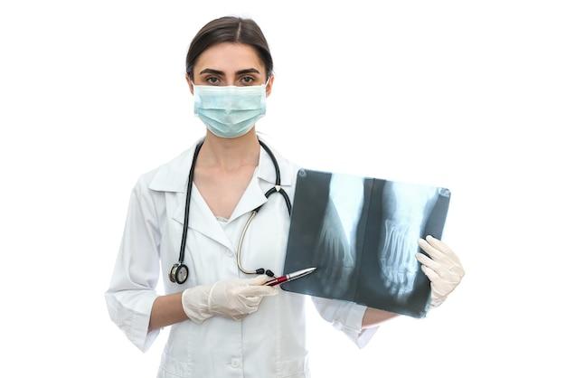 Médico mostrando radiografia de paciente isolada em parede branca