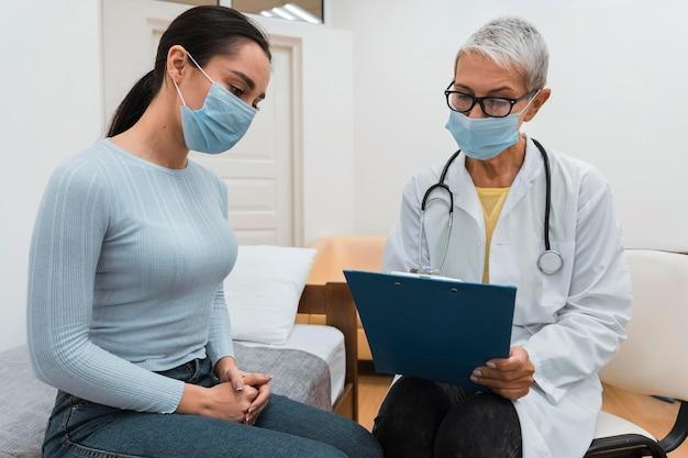 Médico mostrando uma prancheta para um paciente
