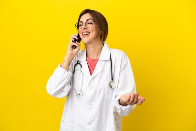 Médico mulher isolada em fundo amarelo, conversando com alguém ao telefone celular