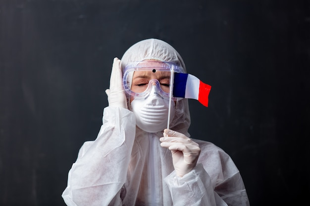 Médico mulher vestindo roupas de proteção contra o vírus com a bandeira da frança