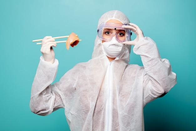 Médico mulher vestindo roupas de proteção contra o vírus detém carne crua com pauzinhos chineses