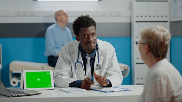 Médico multiétnico e paciente idoso fazendo check-up com tela verde