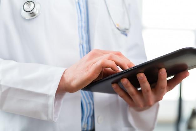 Médico na clínica lendo arquivo digital no computador tablet