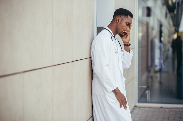 Médico na clínica segurando a cabeça dele tem problemas de saúde e cansado após um dia difícil, deprimido não obteve o resultado desejado, médico afro-americano está triste
